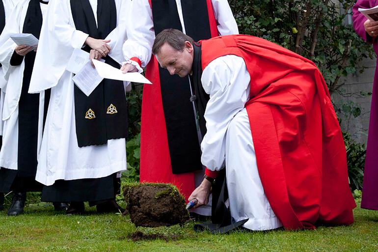The Bishop of Auckland, Ross Bay, turns the first sod at the ground-breaking ceremony.