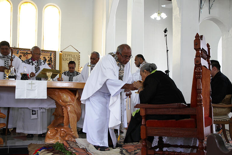 Archdeacon Joe Le'ota administers the chalice to Her Majesty Queen Halaevalu Mata'aho. She was present for the Saturday rededication.