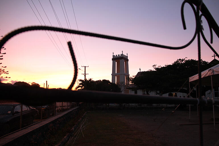 The new St Paul's tower, at dusk, seen through the wrought iron gate to the parking lot next to the church. Marquee at right.