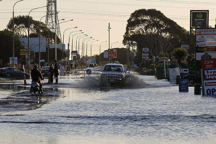 A vehicle drives through floodwater on Ferry Road, Christchurch. Photo: Martin Hunter/Getty Images