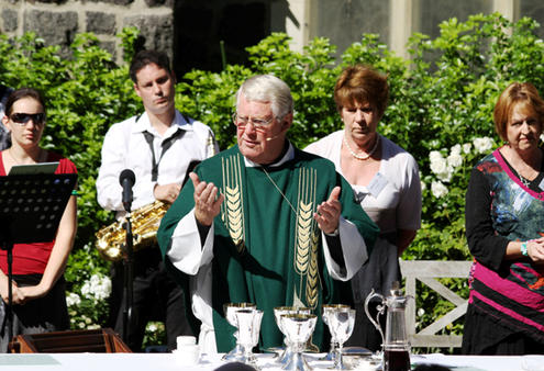 The Rev Philip Robinson, priest assistant at St Barnabas, invites his outdoor congregation to make their communion.