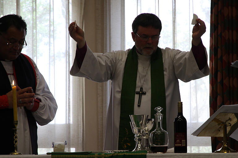 Silhouette of a sacrifice celebrated: Archbishop Philip Richardson presided at the Eucharist.