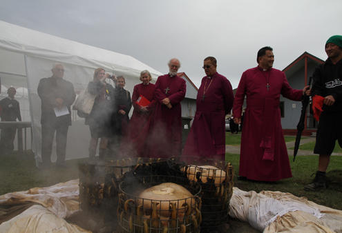 Archbishop Rowan watches as the hangi cooked for the occasion is lifted.