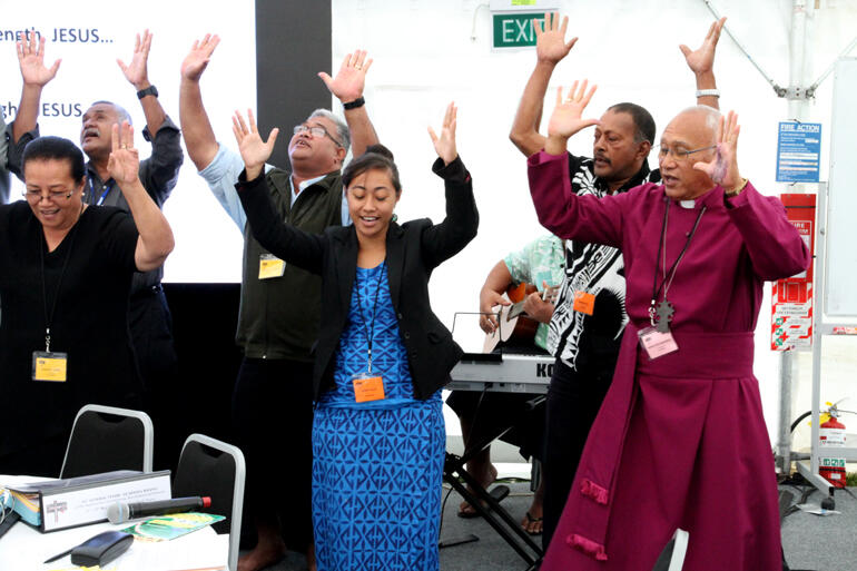 From left: Evelingi Langi and Rosa Filoi dance in support of Archbishop Winston.