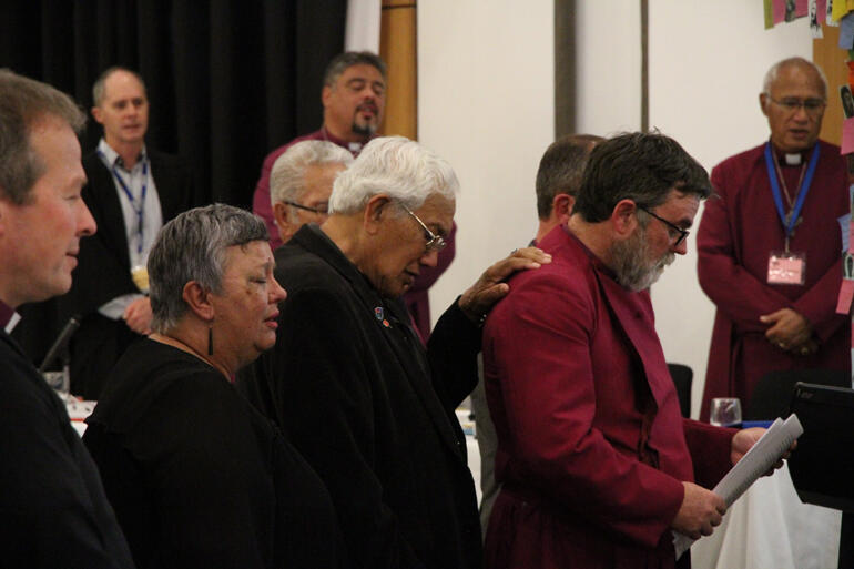 Archdeacon Tikituterangi Raumati backs up Archbishop Philip Richardson as General Synod rises to their feet to make the apology.