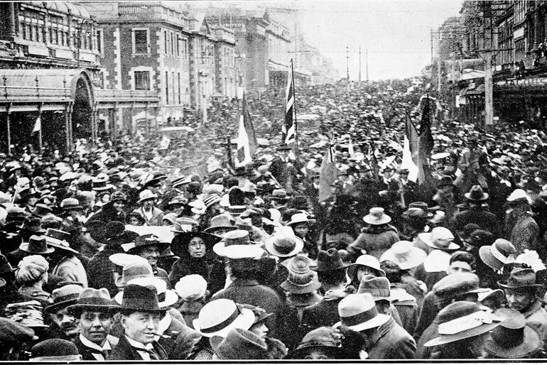 A crowd celebrates Armistice in front of the Stock Exchange, Dunedin 1918. Photo: Sir George Grey Special Collections, Auckland Libraries.