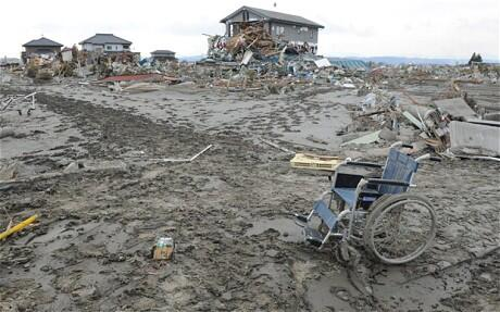 A wheelchair sits forlorn amid the desolation of a town in northern Japan.