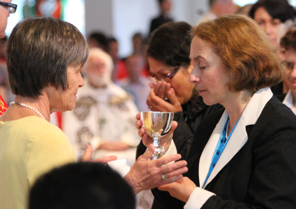 Dr Jane Williams (right), the Archbishop's wife, receives the cup of blessing from Pauline Massey.