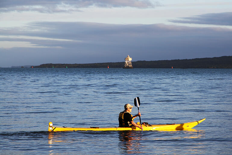 The early morning sun catches Bishop Jim as he glides his kayak in front of the Bean Rock lighthouse.