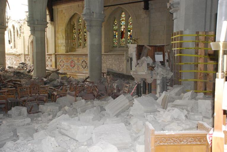 Rubble fills the nave of ChristChurch Cathedral. The pulpit has been partially destroyed.