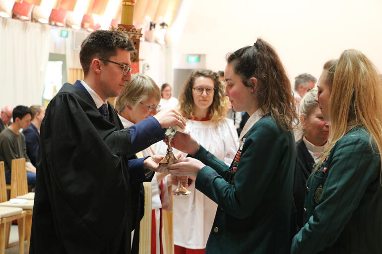 St Margaret's College students Hannah Langley and Virginia Macdonald receive the Eucharist from diocesan Vice Chancellor, Alex Summerlee.