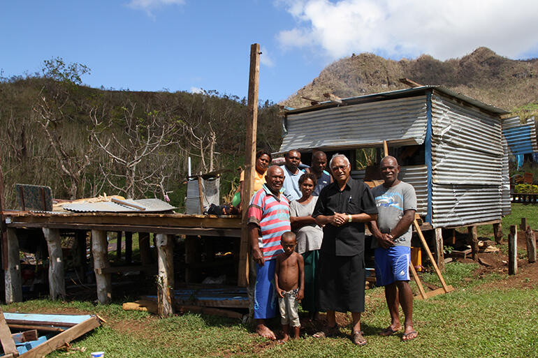Flashback to February: Mosese Kakaramu and Archbishop Winston stand in front of the remains of Mosese's house.