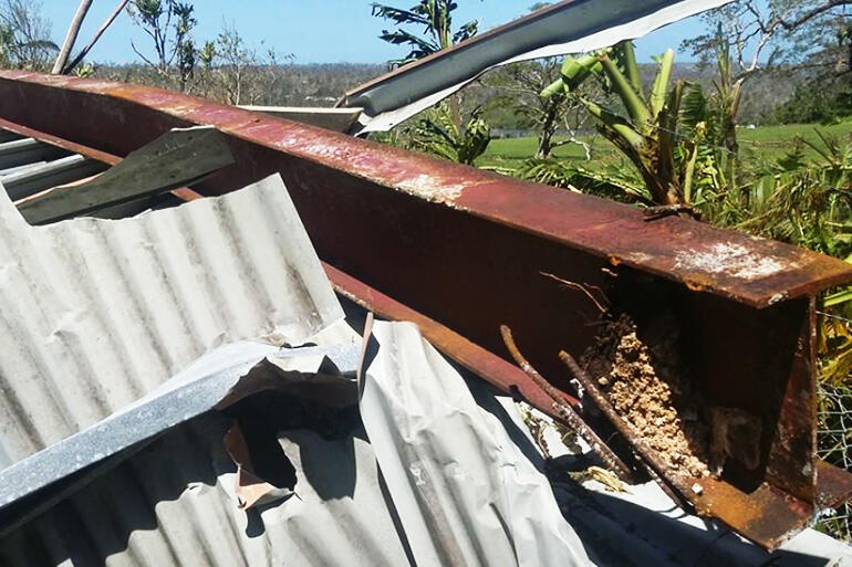 Building down - and a reinforced steel girder, torn from its moorings, sits atop a heap of buckled corrugated iron.