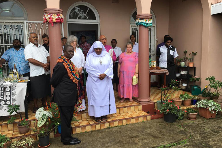 Diocese of Polynesia hosts gather for prayer on the steps of Archbishop Winston's home as they welcome delegates to a Sunday feast.
