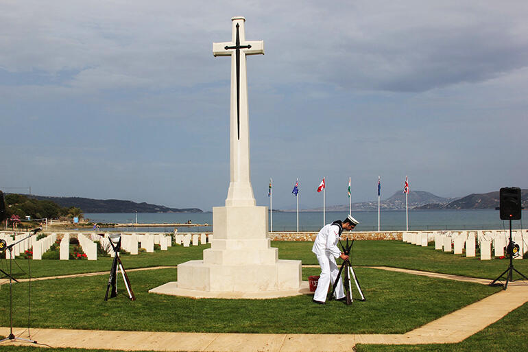 A Greek sailor makes final preparations for the service of remembrance at the Souda Bay War Cemetery.