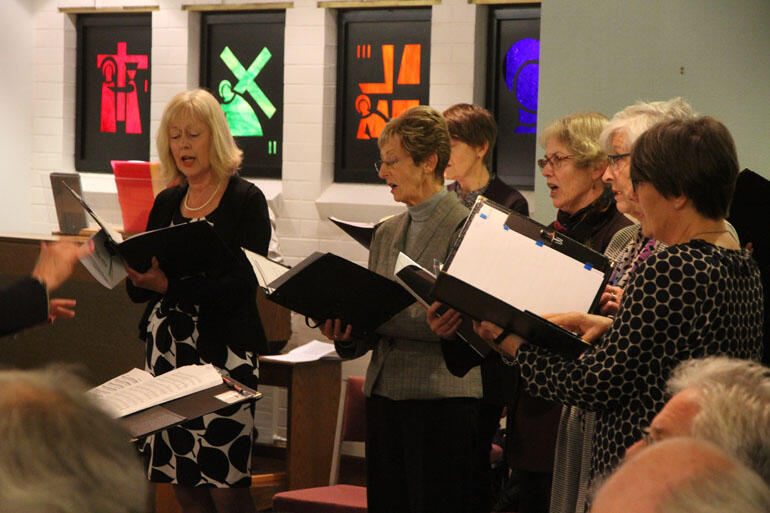 Members of the French music choir directed by Mark Dorrell sing at the Home of Compassion chapel mass.