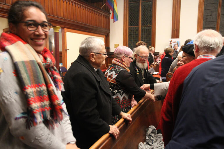 Rev Mele Prescott turns to the camera as her pew mates pass the peace.