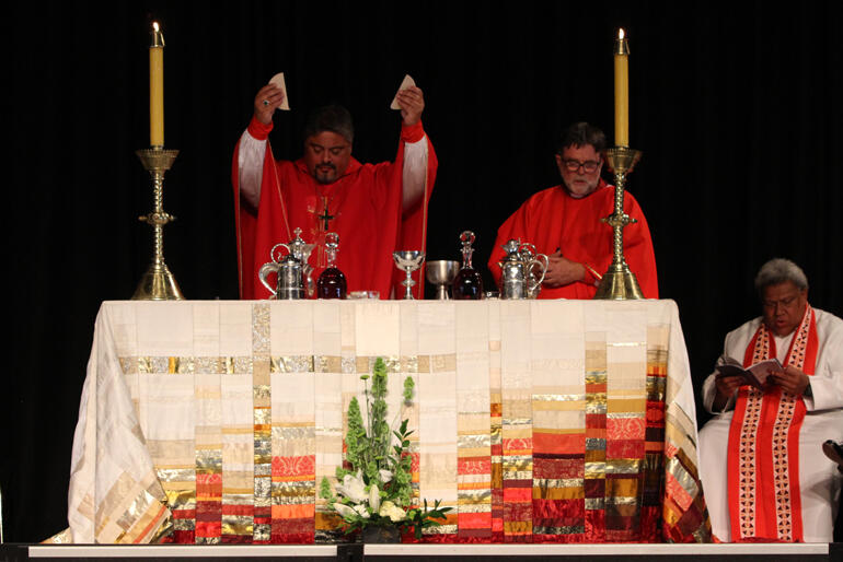 Archbishop Don Tamihere breaks the bread.