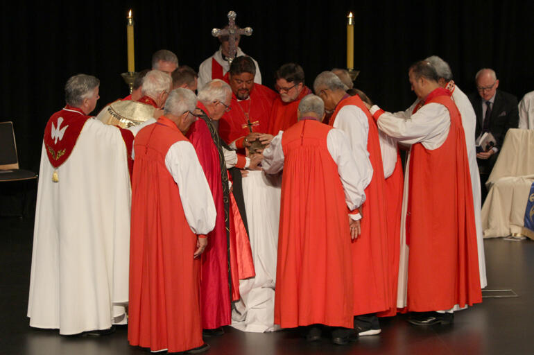 Bishops encircle Peter to ordain him bishop in the laying on of hands.