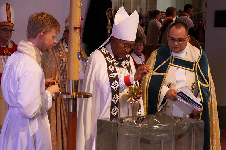 Archbishop Winston blesses the water at the baptismal font. That's Richard Eriksen at left, and Rev Ivica Gregurec.