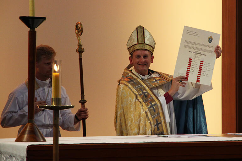 Mission accomplished: a jubilant Bishop Ross Bay holds aloft the Consecration Charter he's just signed.