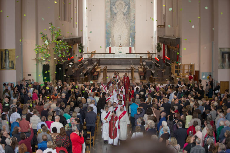 Newly ordained at Wellington Cathedral depart as leaves from the 'tree of life' shower prayers over the congregation. Photo: John Setter