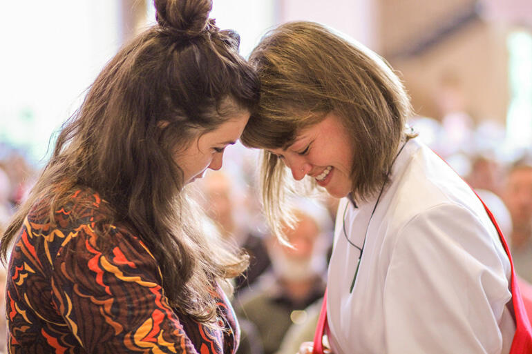 Rev Chelsea Kirby, who serves with Urban Vision in Whanganui, shares a moment with a supporter during her diaconal ordination.