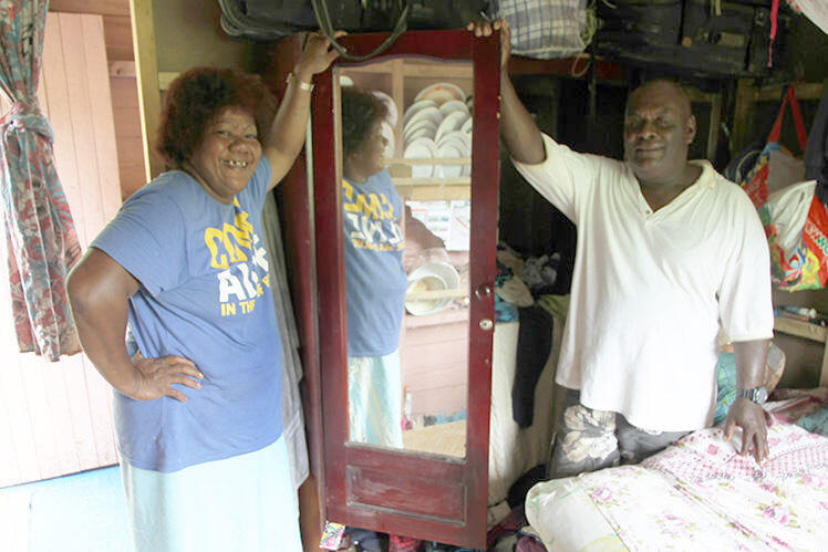 This couple pose by the wardrobe in which they, and two of their children, rode out Cyclone Winston.
