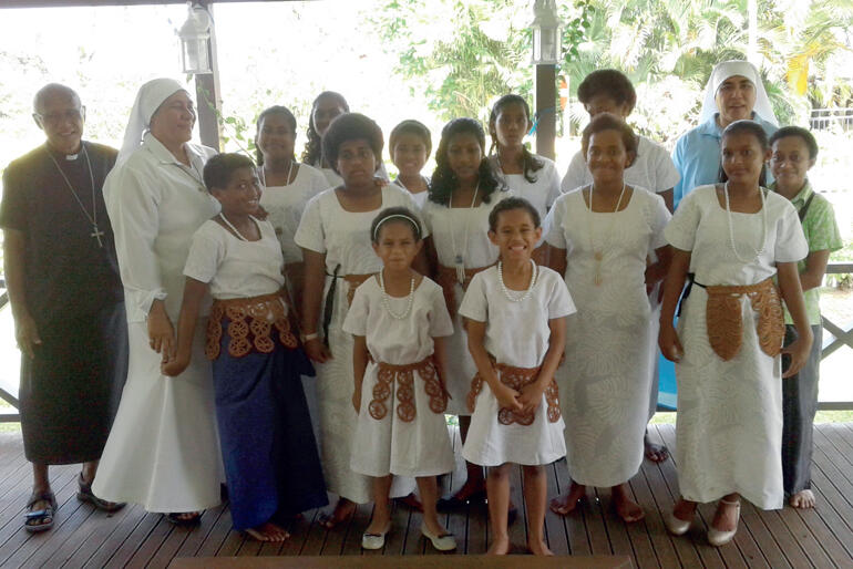 Archbishop Winston Halapua lines up with Sr Vutulongo, Sr Kalolaine and St Christopher's children in their Sunday best.