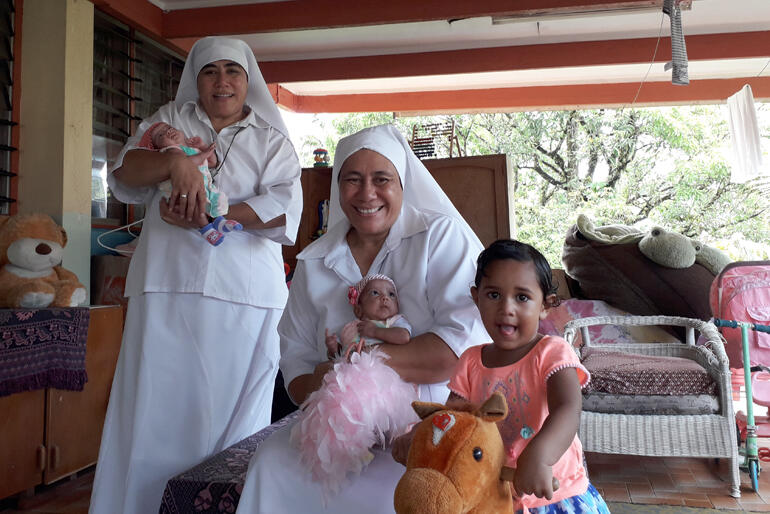 Sr Longo and Sr Kalolaine with two of the babies and a toddler who live at St Christopher's Home in Suva.