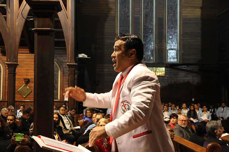 The conductor of the United Church of Tonga at work.